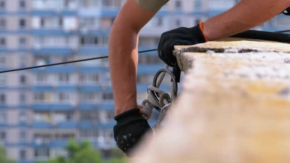 Thumbnail for Industrial Climber in Equipment on Edge of Roof Prepares To Go Down on the Ropes