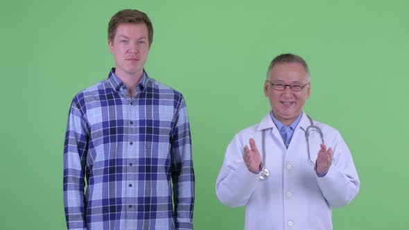Happy Mature Japanese Man Doctor with Young Man Explaining Something Together