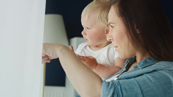 Tilt up video of mother and baby standing next to the window. Shot with RED helium camera in 8K
