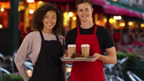 Thumbnail for Zwei multiethnische Kellner posieren für ein Porträt außerhalb Café