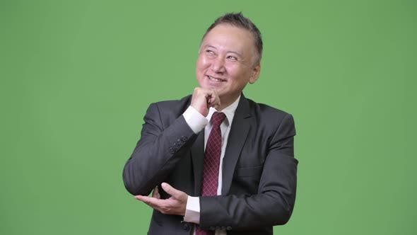Thumbnail for Mature Happy Japanese Businessman Smiling While Thinking