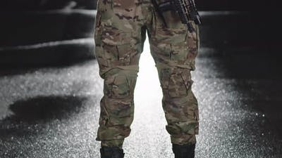 A Soldier in a Special War Uniform Helmet and Gloves Stands in the Dark Leaning Against a Rifle