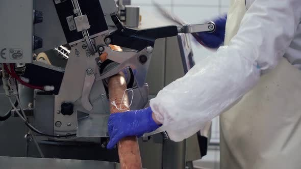 Thumbnail for Worker Separating Sausages Using Machine at Food Factory