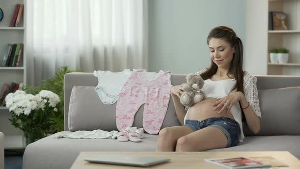 Thumbnail for Schwangere Weibliche hält Teddybär nahe am Bauch, Reiben Sie es sanft, Baby-Spielzeug