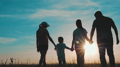 Happy Family Parents and Children Silhouettes Playing on Park