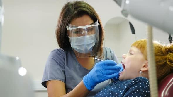Thumbnail for Modern Dentist Office. Portrait of Female Dentist Treating Little Red-haired Girl in Dental Clinic