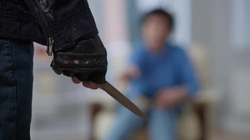 Closeup of Knife in Male Caucasian Hand with Blurred Robbery Victim at Background