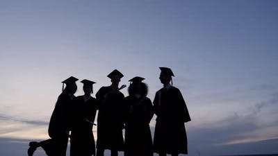 Silhouette of Graduates with Certificates on a Sunset Background