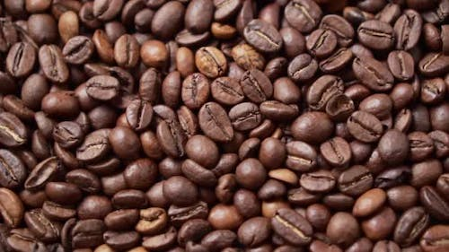 Dark Roasted Coffee Beans Move in a Circle. Close Up.