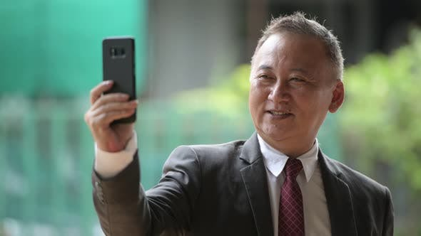 Thumbnail for Mature Japanese Businessman Using Phone in the Streets Outdoors