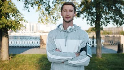 Portrait of Confident Guy in Sportswear Standing Outdoors with Smartphone and Headphones