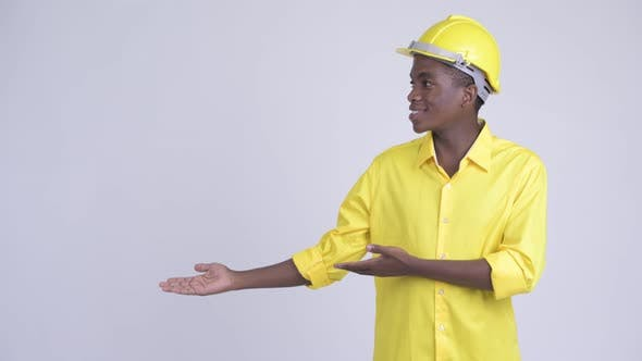 Thumbnail for Young Happy African Businessman As Engineer Showing Something