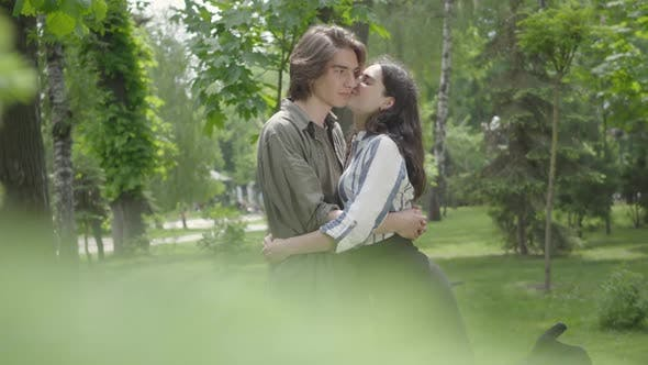 Thumbnail for Cute Young Couple Tenderly Hugging and Kissing in the Background, Blurred Leaves in the Foreground
