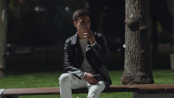 Millennial Guy Sitting on Bench and Smoking Cigarette, Night Walk in City Park, Slow Motion