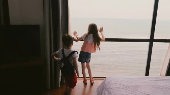 Thumbnail for Two Happy Excited Little Kids Running Up To Large Hotel Apartment Window To Enjoy Incredible Cloudy