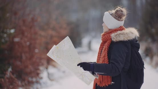 Female Tourist Reading Map in Woods in Winter