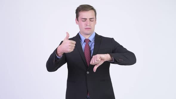 Thumbnail for Young Handsome Businessman Choosing Between Thumbs Up and Thumbs Down