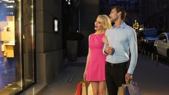 Cover Image for Loving Couple Looking at Showcases with Clothes Discussing Prices and Models