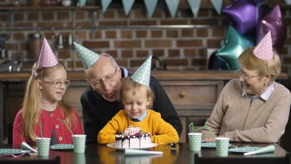 Thumbnail for Boy Blowing Candles on Cake with His Grandparents