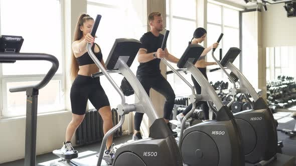 Diverse People Training on Treadmill and Elliptical