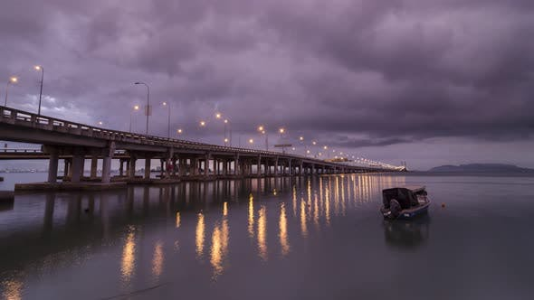 Timelapse Raining morning at the Penang bridge with a traditional boat.