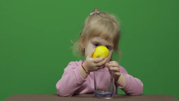 Thumbnail for Schöne junge Mädchen Squeezes Zitronensaft mit ein Grimace auf Ihr Gesicht