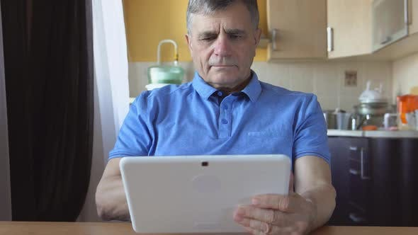 Thumbnail for Aged Male At The Blue Shirt Sits And Uses A White Tablet Pc At Home