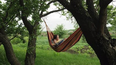 Mother lying in hammock with son
