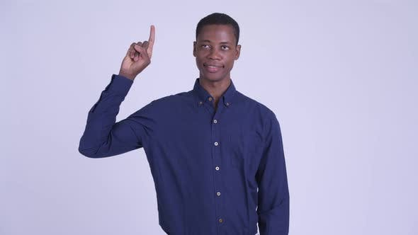 Cover Image for Young Happy African Businessman Pointing Up