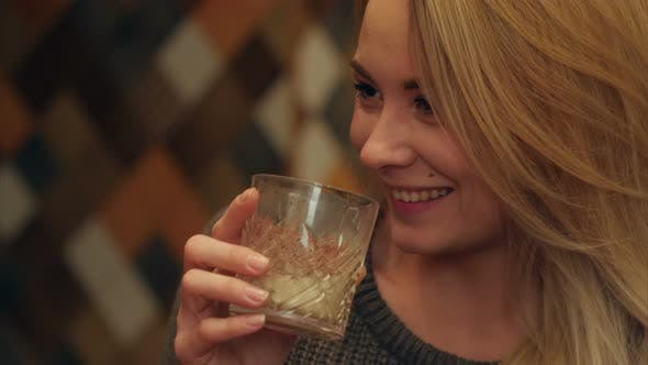 Thumbnail for Young Beautiful Woman Holding a Glass of Drink, Drinking and Laughing