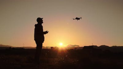 Silhouette of boy flying drone at sunset