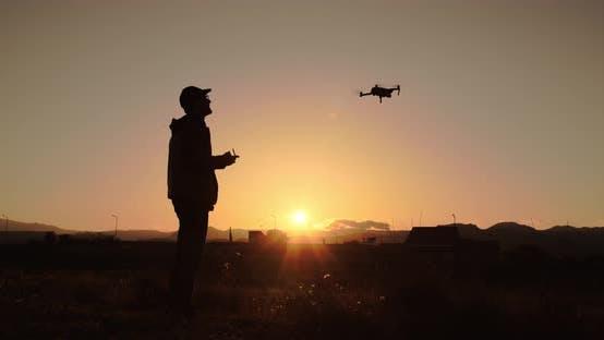 Silhouette de garçon volant drone au coucher du soleil