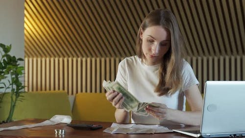 Woman with Calculator Counting Dollar Money at Home