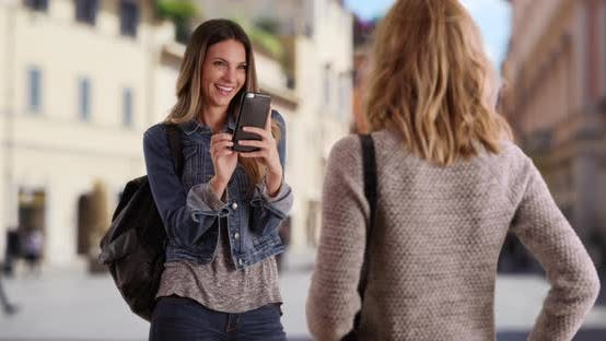 Thumbnail for Young white blonde woman posing while her friend takes a picture on her phone