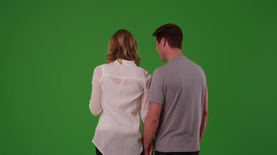 Happy couple shown from behind embracing, standing on green screen