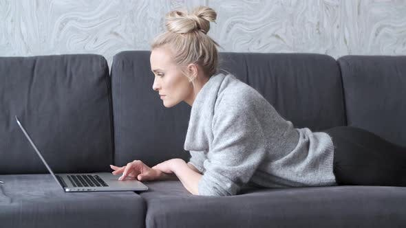 Thumbnail for Happy Blond Woman Lying Prone on Sofa and Working on Laptop Computer