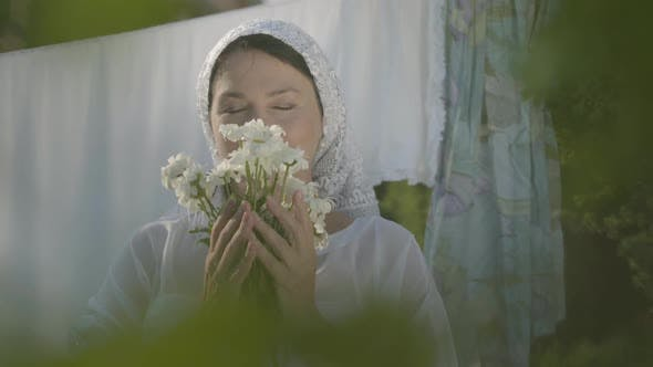 Thumbnail for Adorable Woman with White Shawl on Her Head Sniffing Daisies Looking at Camera Near the Clothesline