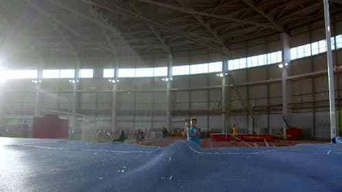 Pole Vaulting - Young Guy in Blue t Shirt Is Running and Jumping Over the Bar