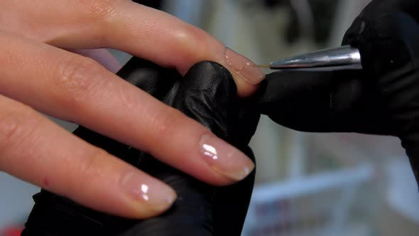 Experienced Beautician Applies Gel on Young Woman Fingernail