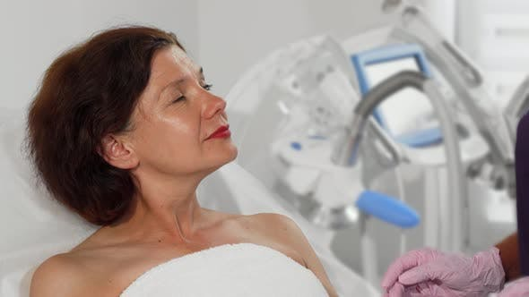 Middle Aged Woman Getting Her Skin Examined By Dermatologist
