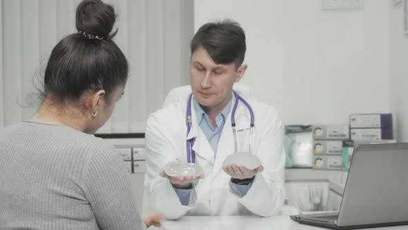 Plastic Surgeon Showing Types of Silicone Breast Implants to the Patient