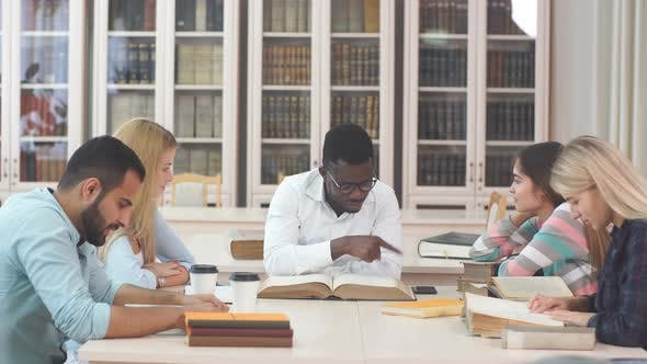 Thumbnail for Multiethnic Young People Sitting at Table Reading Reference Books for Study Notes