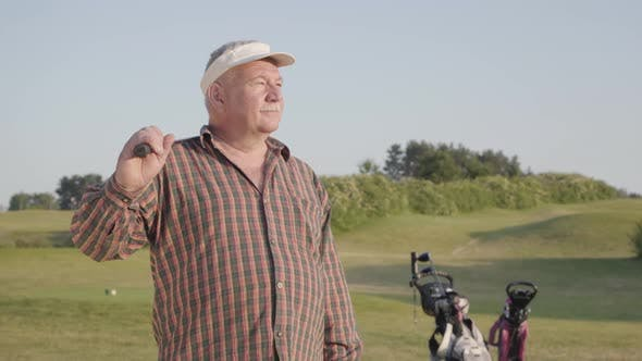 Thumbnail for Portrait of a Confident Successful Mature Man with a Golf Club Standing on a Golf Course in Good