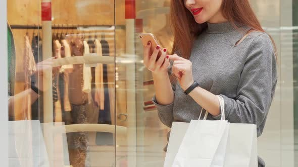Thumbnail for Woman Smiling Browsing on Her Smart Phone While Shopping at the Mall