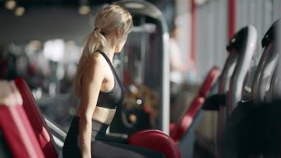 Athlete Woman Training Muscle on Sport Simulator in Modern Gym Club