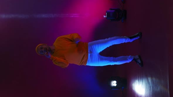 Thumbnail for Vertical Video. Incendiary Funny Singer in Yellow Clothes Dancing and Singing with a Microphone in