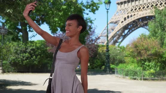 Cheerful mixed race woman takes selfies on smartphone in front of Eiffel Tower