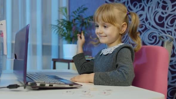 Child Girl Calling To Teacher on Laptop Distance Education Learning at Home on Coronavirus Lockdown
