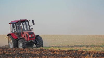 Tractor plows a field. Close up of tractor cultivating field