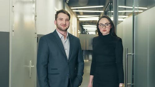 Portrait of Two Business People Man and Woman Standing in Business Center and Looking at Camera